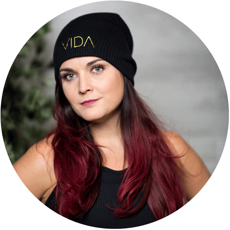 Tonya Tucker headshot. Tonya slightly smiles into the camera. She is wearing a black tank top, a black beanie cap with VIDA embroidered on the front. Her long dark-red hair rests on her shoulders
