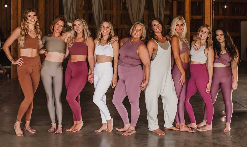 a group of women in yoga clothing stand together in a studio space, all smiling at the camera